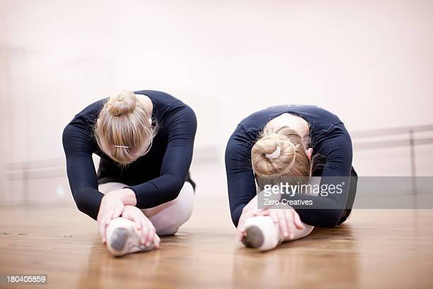 Two ballerinas in pose on studio floor