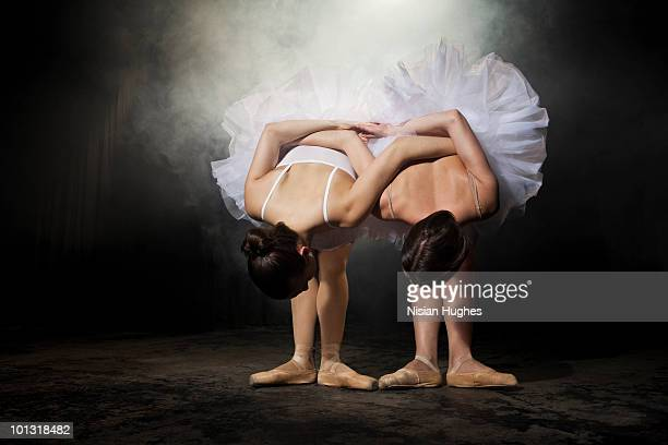 Two ballerinas stretching on stage