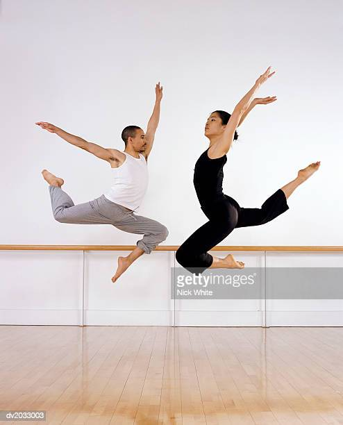 Two Ballet Dancers Jumping Mid Air With Their Arms Raised and Looking Face to Face