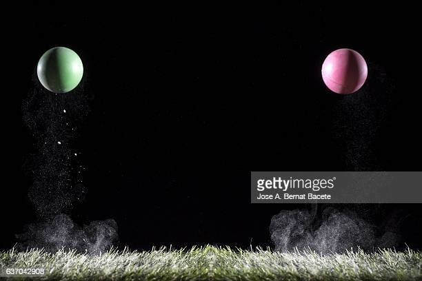 two balls impacting on a surface of grass grass with powder - bouncing ball stock photos and pictures