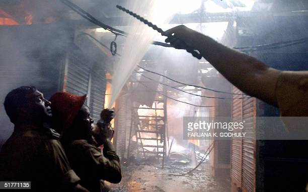 Two Bangladeshi firemen train their hoses on burning shops at a market in down town Dhaka 21November 2004 At least one person was killed when a huge...
