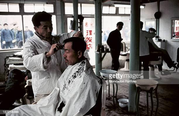 Two barbers cut customers' hair at the same time in a big hairdressershop in Peking Peking January 1973