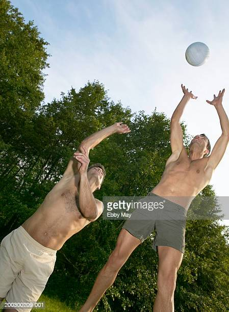 Two bare chested men jumping for ball outdoors
