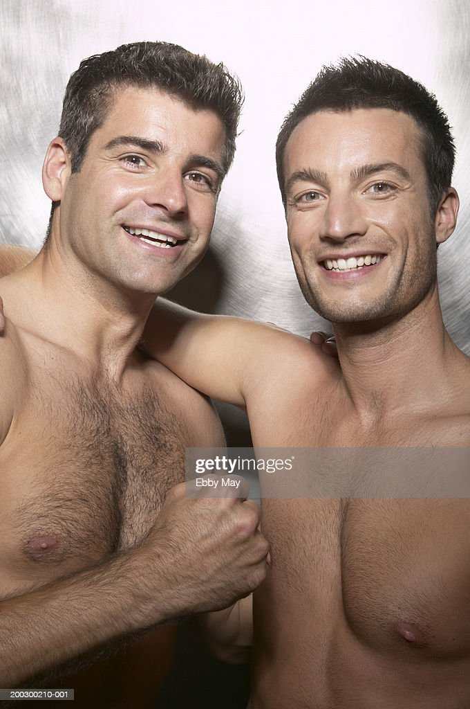 Two Bare Chested Men Standing Arm In Arm Smiling Portrait