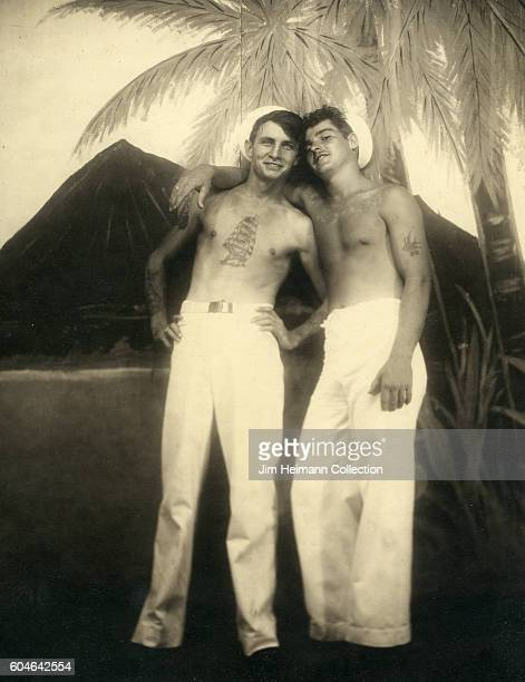 Two bare chested sailors with tattoos standing for tropical arcade photo depicting palm tree and Diamondhead
