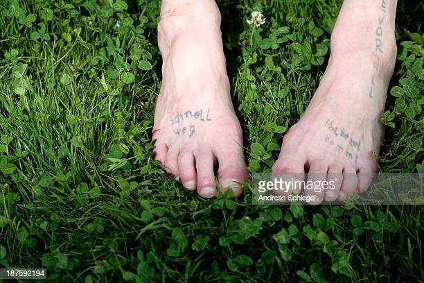 Two bare feet with faded tattoos on them
