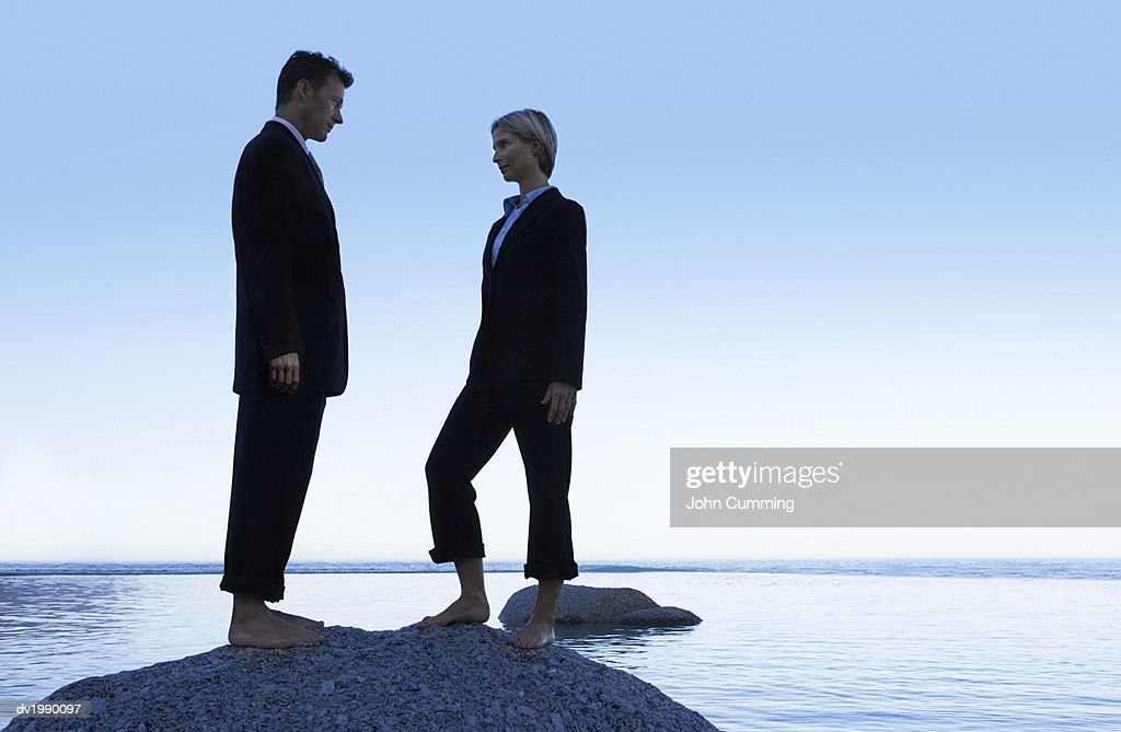 Two Barefoot Business Executives Standing Face to Face on a Rock in the Sea : Stock Photo