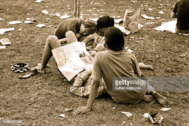 Two bare-footed couples with tambourine rested on the littered grass at the 1st Elysian Park Love-In on March 26, 1967 in Los Angeles, California.