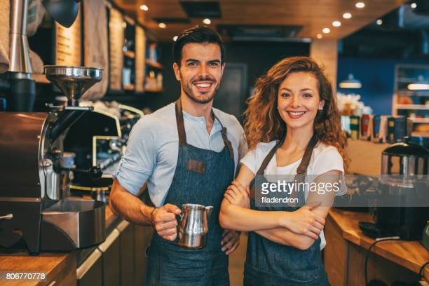 two baristas - coffee grinder stock photos and pictures