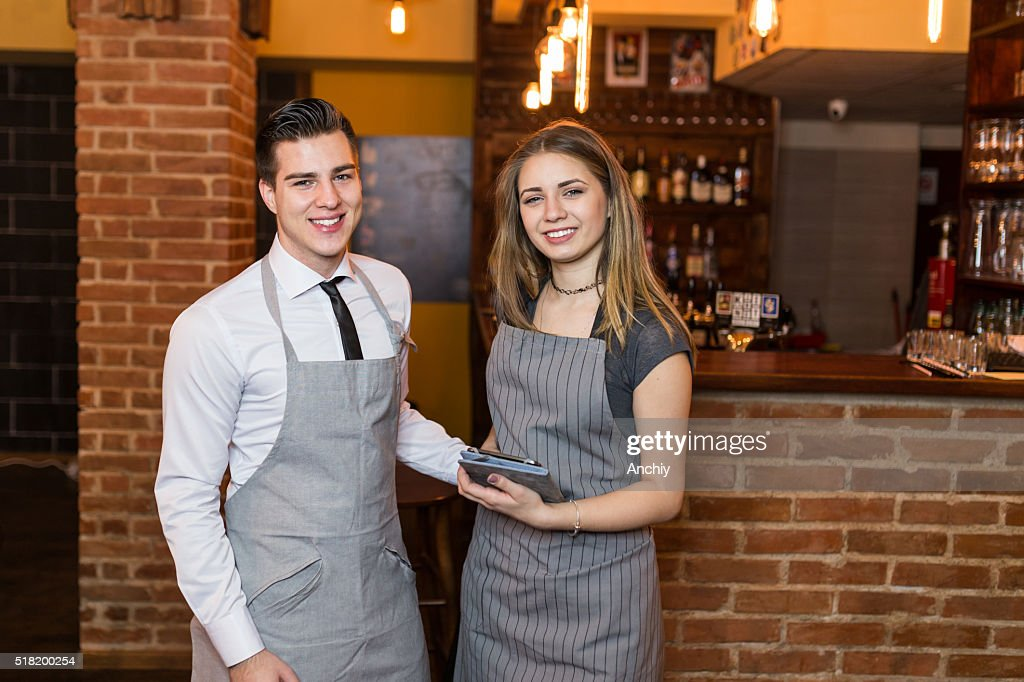 Two baristas smiling at the camera at the cafe : Stock Photo