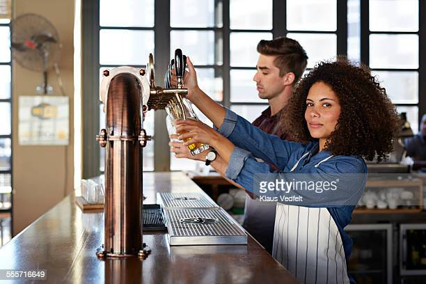two bartenders pouring beer at microbrewery - bec photos et images de collection