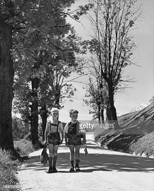 Two Bavarian boys on their way home from school in the Bavarian Alps Germany circa 1950 The snowcapped Watzmann mountain is visible behind them