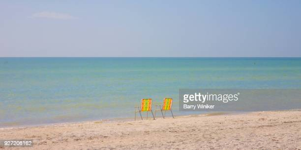 Two beach chairs at water's edge on Sanibel Island