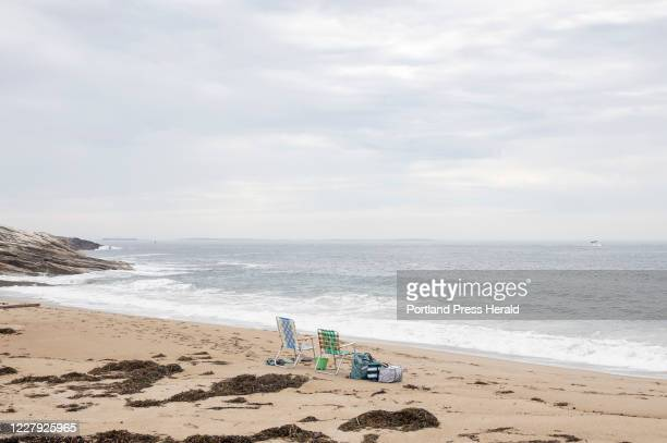 Two beach chairs sit near the surf at Reid State Park on Thursday, July 30, 2020. The park restricted swimming to knee depth only in response to the...