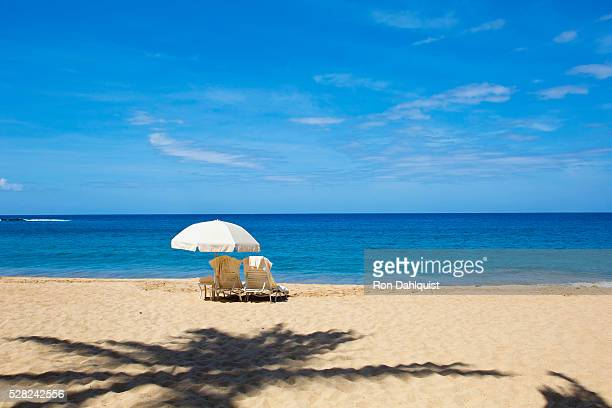 two beach chairs with umbrella on hulupo'e beach, manele bay; lanai, hawaii, united states of america - lanai stock photos and pictures