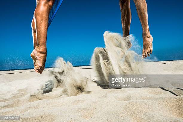 two beach volleyball players jumping mid air in sand - beachvolleybal stockfoto's en -beelden