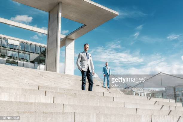 two bearded elegant businessmen on concrete stairs outdoors in Berlin