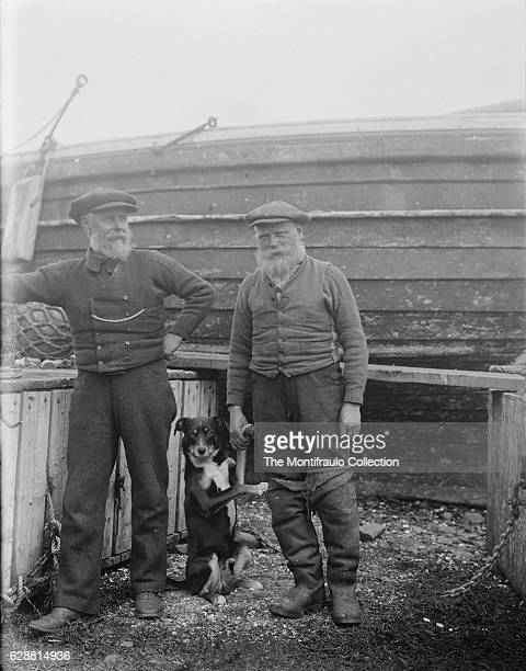 Two bearded fisherman one wearing waders holding the the front paw of a dog standing between them Behind them is a wooden boat hull 11th July 1916