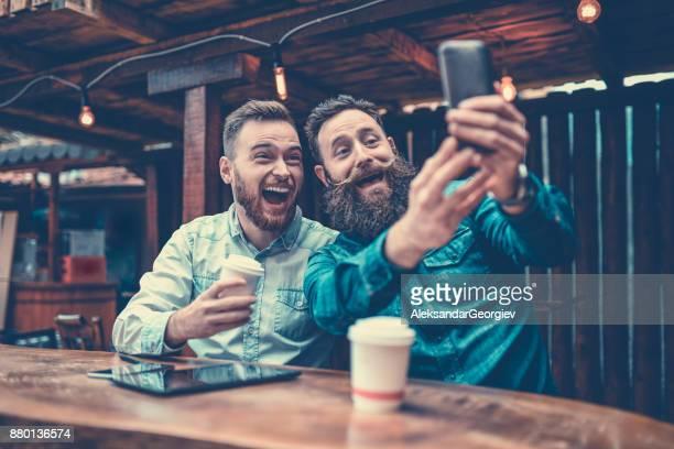 Zwei bärtigen Freunde, trinken Kaffee und nehmen Selfie in Cafe