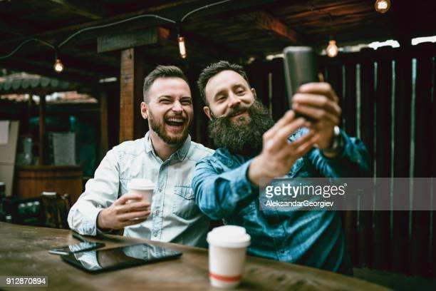 Zwei bärtigen Freunde, trinken Kaffee und nehmen Selfie in Kaffee