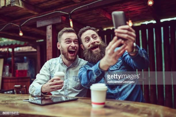 zwei bärtigen freunde, trinken kaffee und nehmen selfie in restaurant - mann kaffee stock-fotos und bilder