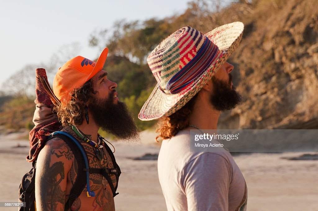 Two bearded travelers stroll along the beach : Stock Photo
