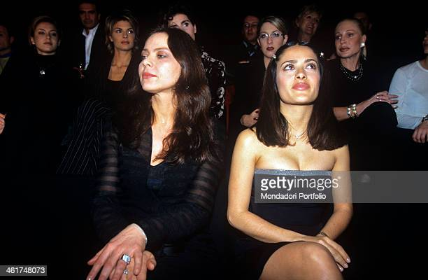 Two beautiful actresses seated side by side in the front row before the catwalk of Giorgio Armani's parade at the fashion week seem to ignore each...