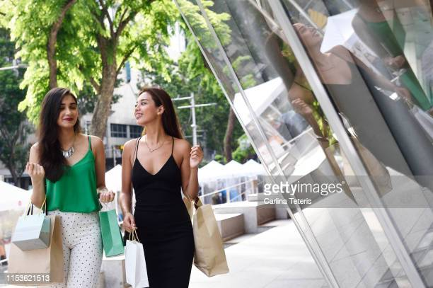 two beautiful asian women shopping on orchard road - orchard road fotografías e imágenes de stock