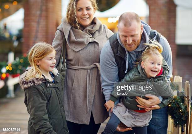 Two beautiful blonde sisters with blonde mother and redhead father at winter christmas market