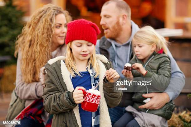 Twee mooie blonde zusters met blonde moeder en vader van de roodharige op winter kerstmarkt
