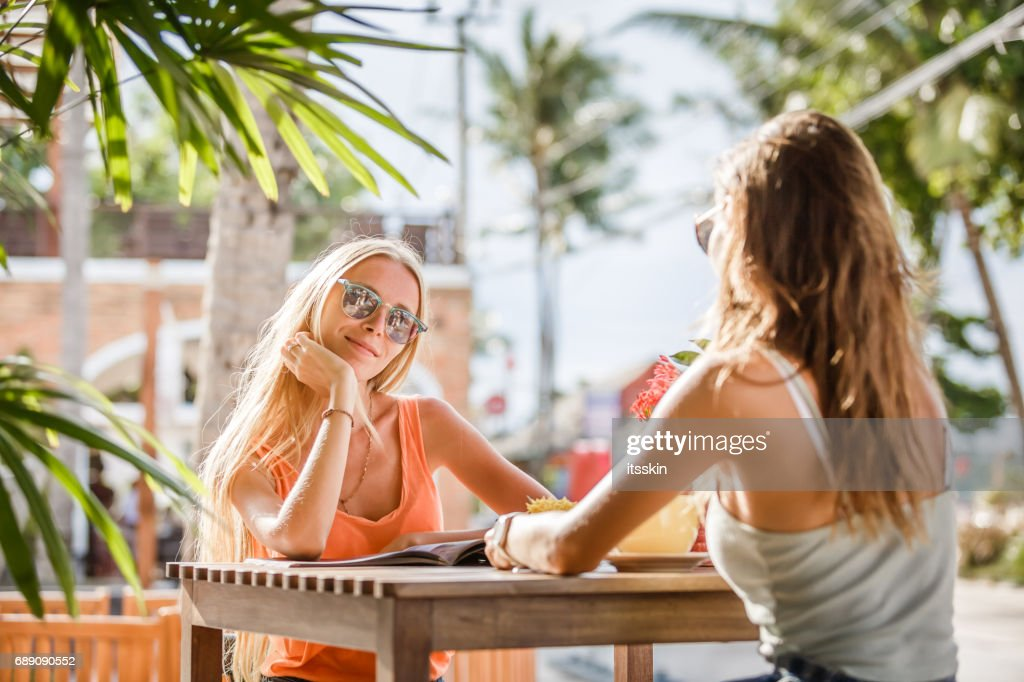 Two beautiful brunette girlfriends chat in a cafe : Stock Photo