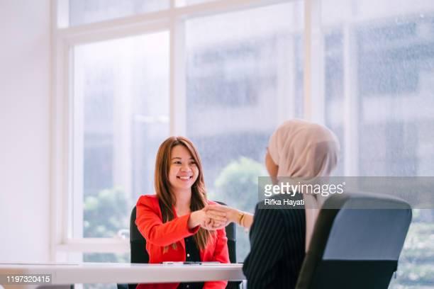 two beautiful businesswomen handshake - rifka hayati stock pictures, royalty-free photos & images