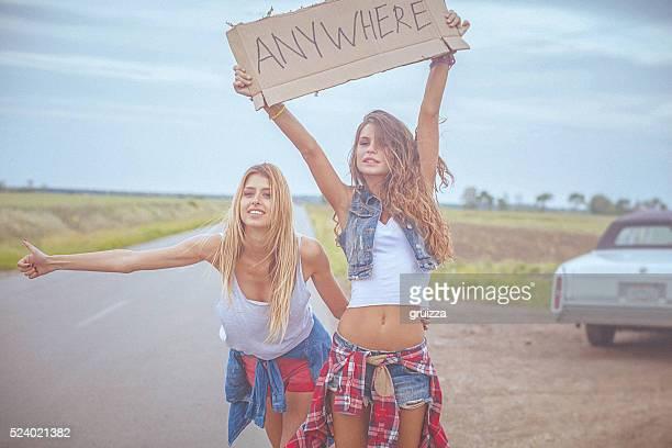 Zwei wunderschöne fröhlich hipster Freunde Trampen an der road