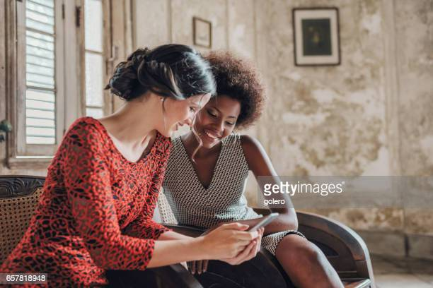 two beautiful elegant young cuban woman looking at mobile in old house