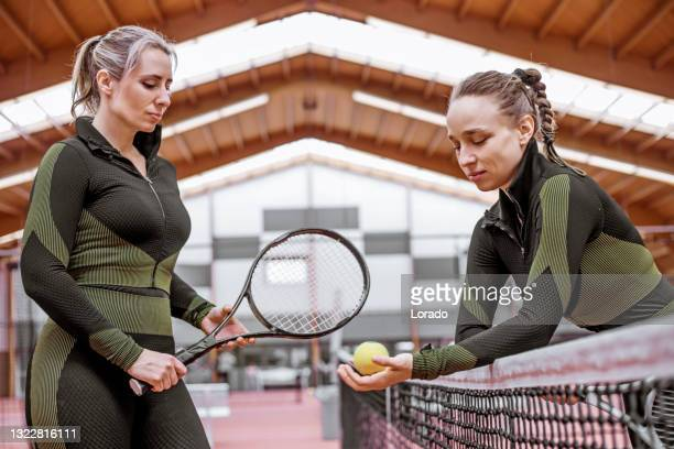 two beautiful female tennis players on the indoor court - international match stock pictures, royalty-free photos & images
