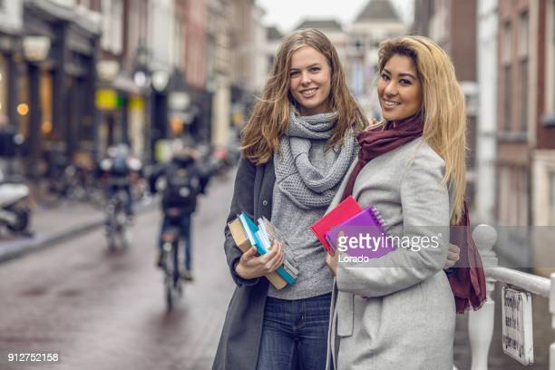 Twee mooie vrouwelijke Universiteit student vrienden in de Nederlandse stadscentrum