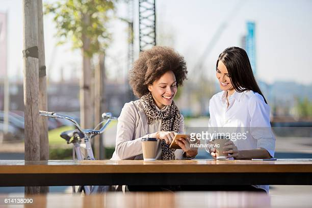 Two beautiful females drinking coffee to go