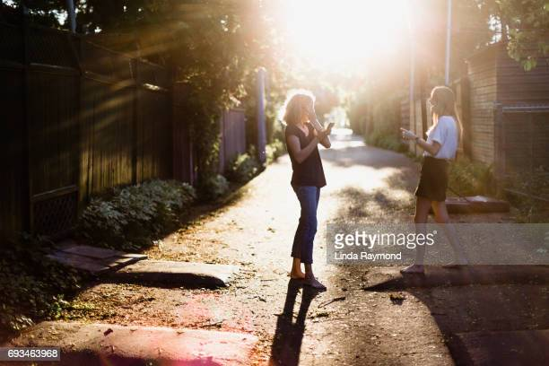 Two beautiful girls in an alley at sunset looking at her cellphone