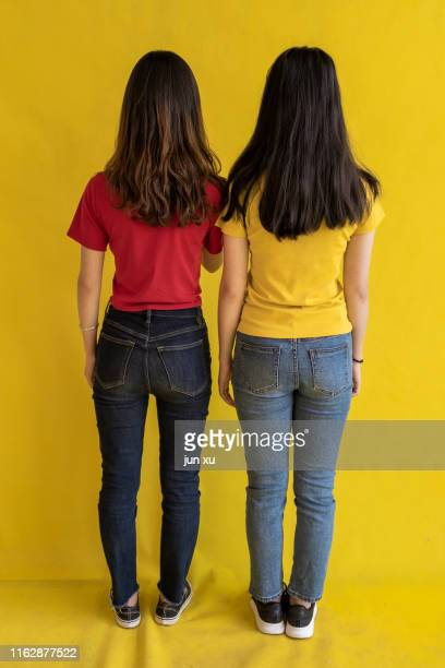 two beautiful girls in red and yellow embraced each other - fesse enfant photos et images de collection