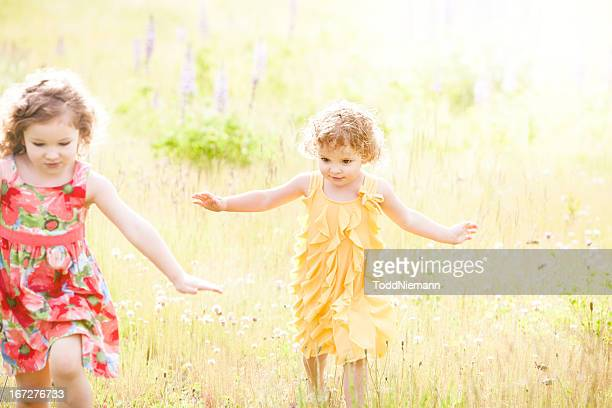 two beautiful girls running through flower field - long bright yellow dress stock pictures, royalty-free photos & images