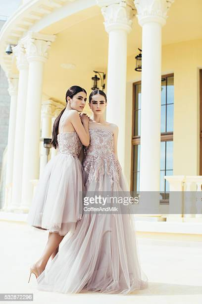 Two beautiful girls wearing dresses