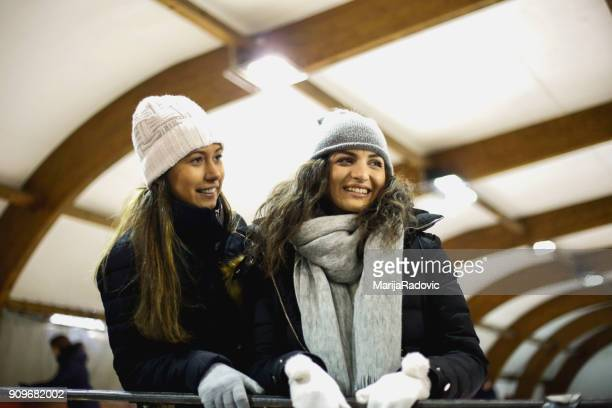Two beautiful girls wearing warm winter clothes ice skating