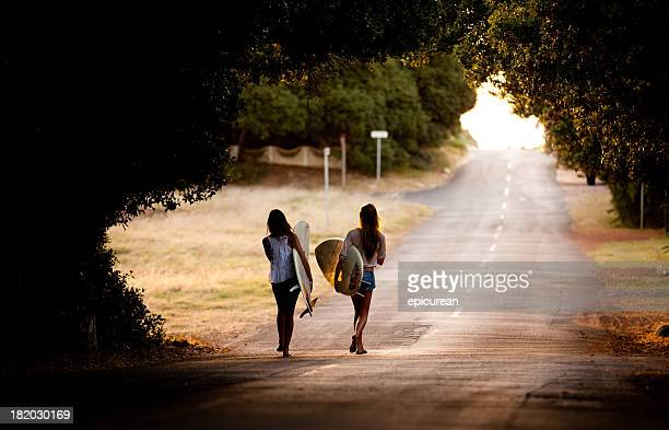 Two beautiful healthy young women going for a surf together