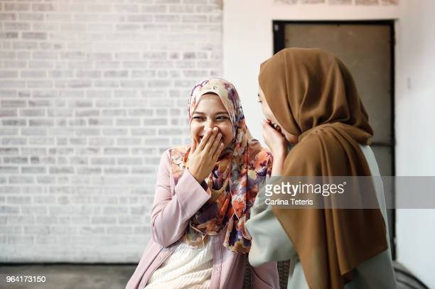 two beautiful malay ladies chatting indoors - malaysian culture stock pictures, royalty-free photos & images