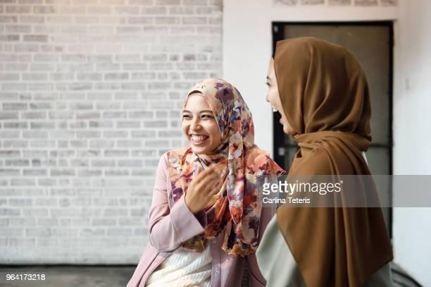 two beautiful malay ladies chatting indoors - zurückhaltende kleidung stock-fotos und bilder
