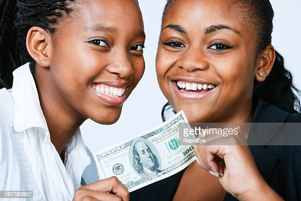 Two beautiful, smiling young women with $100 bill