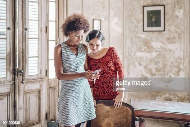 zwei schöne stilvolle junge kubanische Frau betrachten Mobile im Innenbereich