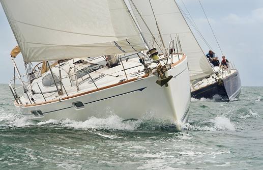 Two beautiful white yachts, sailboats or sail boats sailing or racing at sea 1071351368