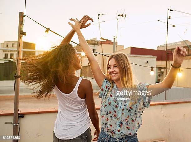 Two beautiful woman dance at sunset in a rooftop party.