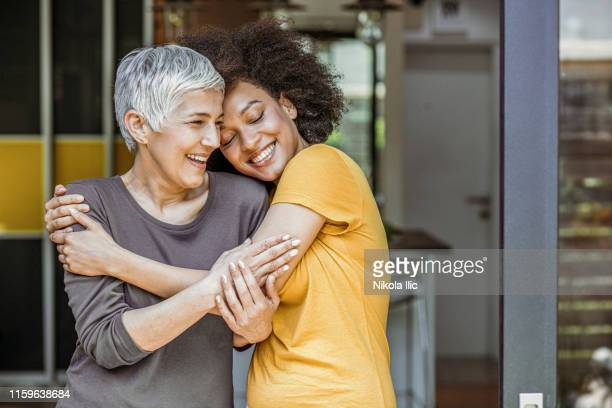 two beautiful woman embracing - sostegno morale foto e immagini stock
